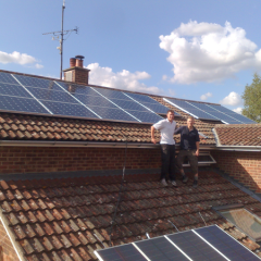 Two men stood in front of solar panels on roof at Capel St Mary