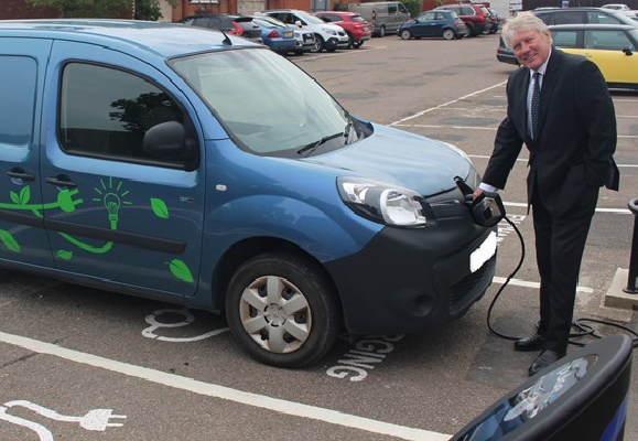 Man in suit charging an electric vehicle