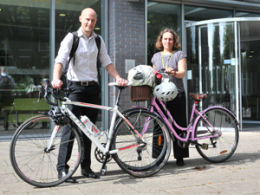 Two cyclists with bicycles outside the front of a business building